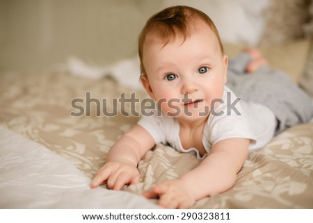 sweet little baby boy lying on the bed - stock photo
