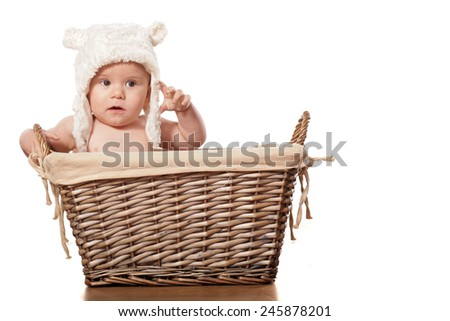 sweet little baby boy sitting in a wicker basket
