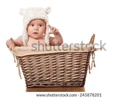 sweet little baby boy sitting in a wicker basket - stock photo