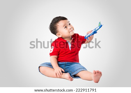 sweet little baby dreaming of being pilot. Cute little asian boy playing with a toy airplane - stock photo