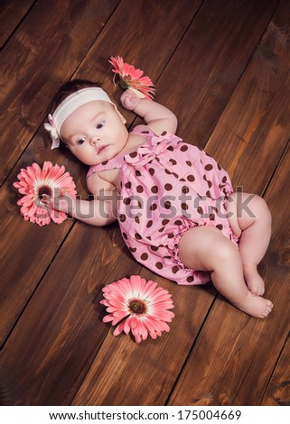 Sweet little baby girl crawling on a wooden floor - stock photo