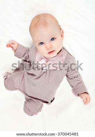 Sweet little baby girl in striped pink costume laying on white background. Top view. - stock photo
