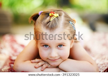 Sweet little baby girl lying on a blanket in the park. Close-up of child resting her head on her hands and looking into the camera. Shallow depth of field. Selective focus. - stock photo