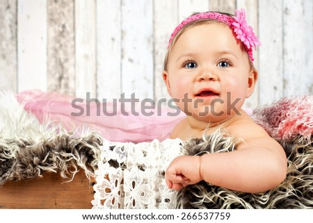 sweet little baby sitting in an old wooden crate with blanket - stock photo