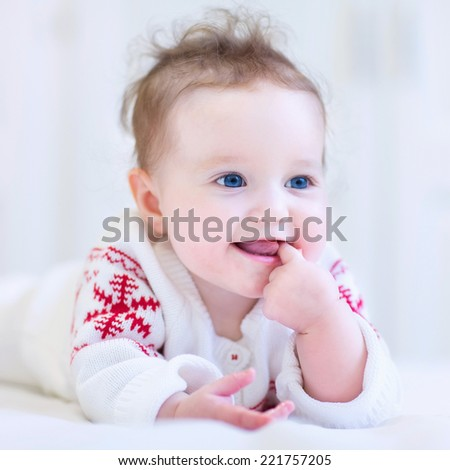 Sweet little baby wearing a knitted sweater with red Christmas ornament - stock photo
