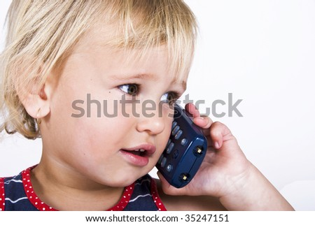 Sweet little blond girl talking on the telephone - stock photo