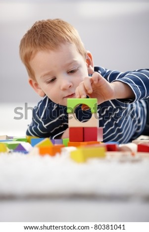 Sweet little boy building tower from cubes at home, laying on floor.? - stock photo