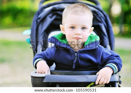 Sweet little boy in the pram outdoors - Closeup