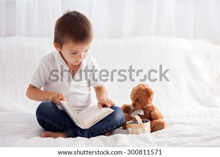 Sweet little boy, reading a book in bed and eating blueberries, teddy bear next to him on the bed - stock photo