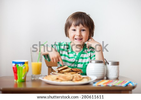 Sweet little caucasian boy, eating pancakes and drinking orange juice at home - stock photo