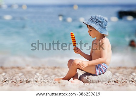 Sweet little child, boy, eating ice cream on the beach, summertime - stock photo