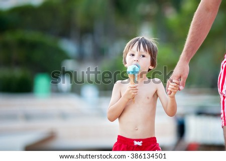 Sweet little child, boy, eating ice cream on the beach, walking on the beach hand in hand with dad - stock photo