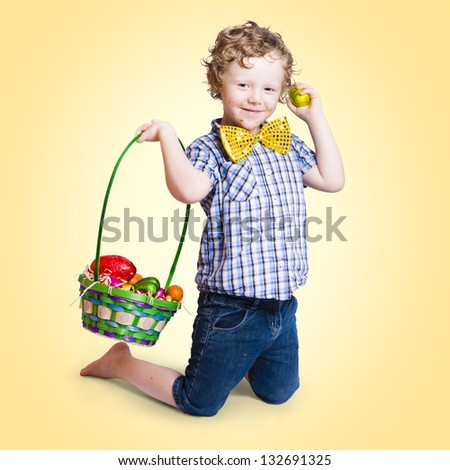 Sweet little child holding easter present with basket full of colourful easter eggs on yellow gradient background