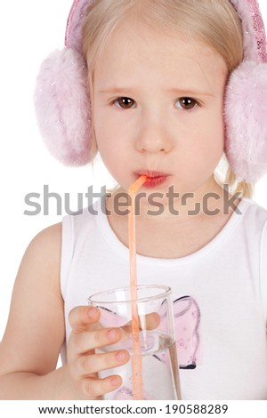sweet little child in the delicate pink dress and fur headphones drinking water