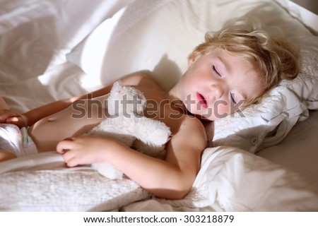 Sweet little child sleeping in bed. Healthy kid, blonde toddler girl, resting in bed in white sunny bedroom. - stock photo