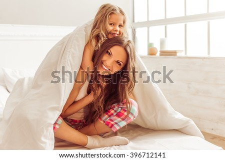 Sweet little girl and her beautiful young mother are hugging, looking at camera and smiling while sitting on bed under the blanket - stock photo