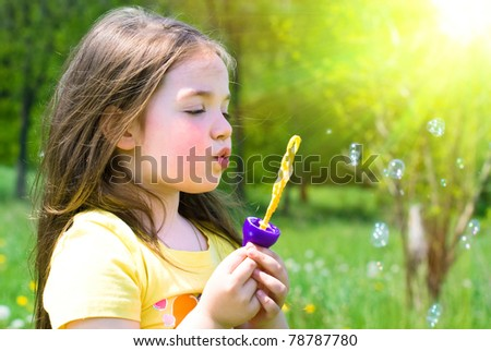 sweet little girl blowing bubbles on the meadow - stock photo