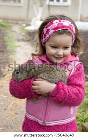 Sweet little girl hold a rabbit in the farm. - stock photo