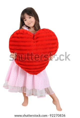 sweet little girl holding large red heart cushion, isolated on white - stock photo