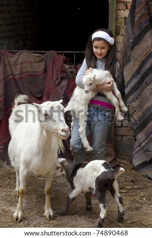 Sweet little girl in a farmyard with baby animals - stock photo