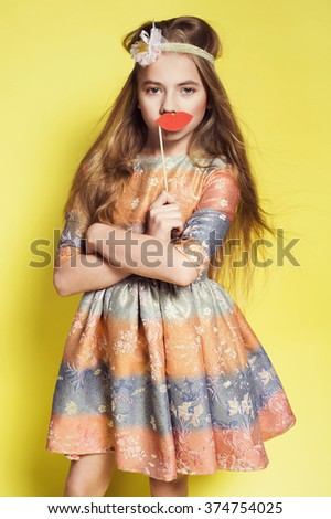 Sweet little girl in a nice dress holding paper red lips. Kid fashion photo. Long hair style - stock photo