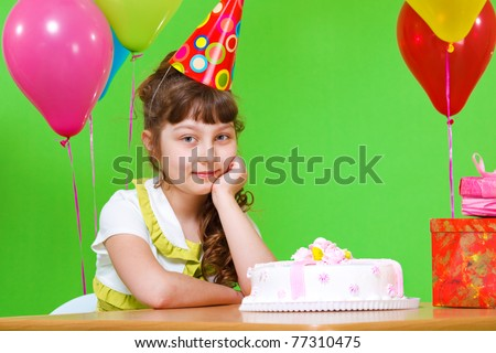 Sweet little girl in a party hat sits at the table