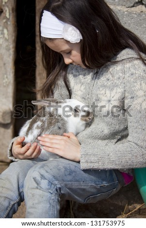 Sweet little girl in the farm yard with little baby rabbit