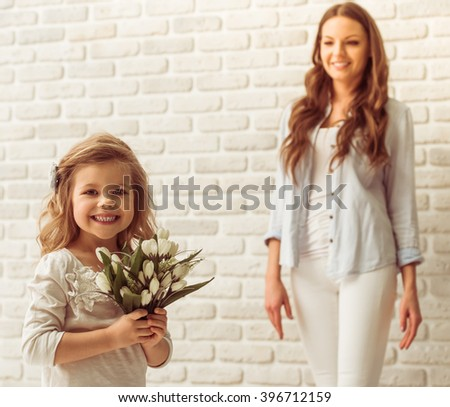 Sweet little girl is holding flowers, looking at camera and smiling, her beautiful young mother in the background - stock photo