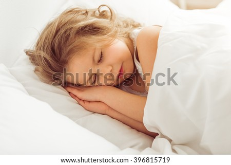 pic stock photo gigging young adult woman wearing jeans and sweater in prone position on white sofa