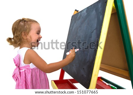 Sweet little girl learning happily in front of her blackboard - stock photo