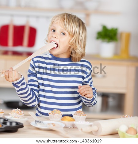 Sweet little girl licking a wooden spoon while standing at a kitchen counter baking cupcakes - stock photo