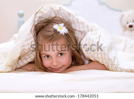 Sweet little girl lying down in the bed covered with blanket, cute flower in hair, sleeping in child bedroom, happy childhood concept - stock photo