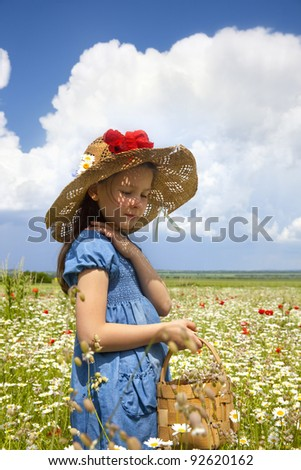 Sweet little girl on the wild field with blossom flowers. - stock photo