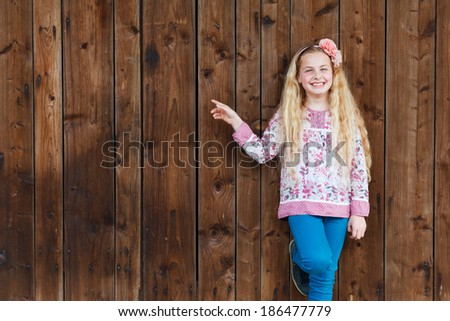 sweet little girl presenting copy space - stock photo