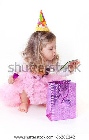 Sweet little girl reading birthday greeting card - stock photo