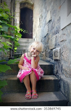 Sweet little girl sitting on the stairs steps - stock photo
