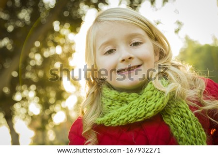 Sweet Little Girl Wearing Winter Coat and Scarf Outdoors at the Park.  - stock photo