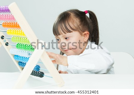 Sweet little girl with Down Syndrome, playing with wooden abacus - stock photo