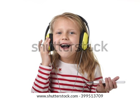 sweet little girl 7 years old with blonde hair and blue eyes listening to music with headphones and mobile phone singing and dancing happy isolated on white background - stock photo