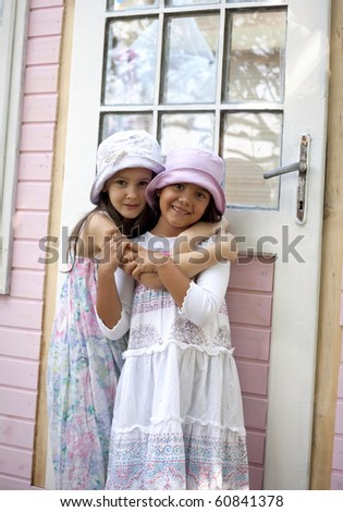 Sweet little girls in front of her little house for playtime - stock photo