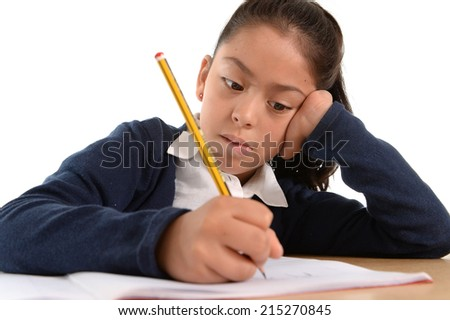sweet little hispanic female child writing carefully homework with pencil with  concentrated face in children education and back to school concept isolated on white background - stock photo