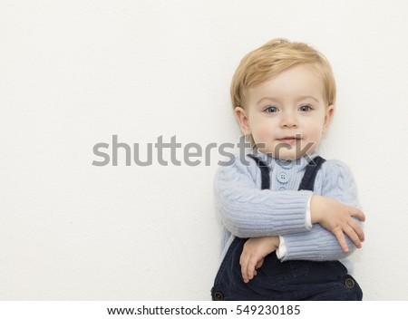 Sweet little kid standing with arms crossed over white background