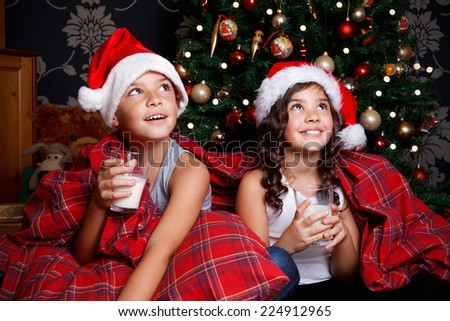 Sweet little kids drinking milk in the bed - stock photo