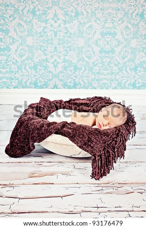 Sweet little newborn baby sleeping in bowl with wooden floor and blue background - stock photo