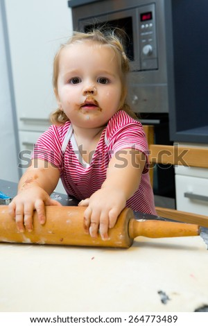 Sweet little one year old girl is learning cooking in the home kitchen. - stock photo