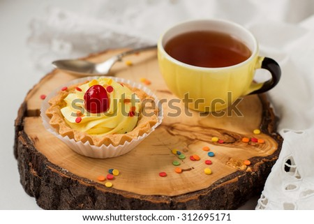 sweet little pastry with a mug on rustic wooden background - stock photo