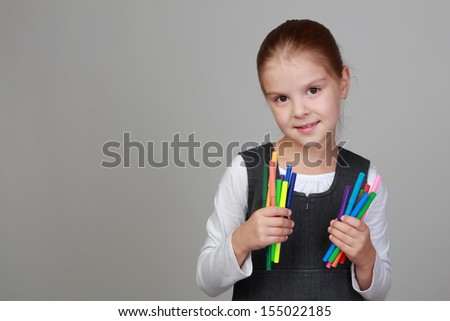 Sweet little schoolgirl holding felt tip pens on Education
