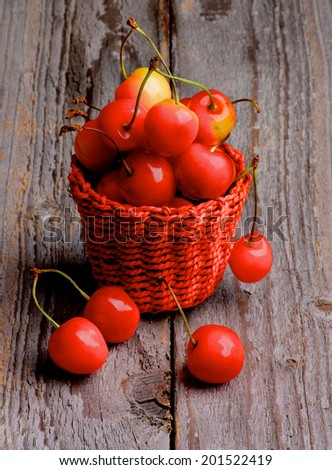 Sweet Maraschino Cherries in Red Wicker Basket isolated on Rustic Wooden background - stock photo