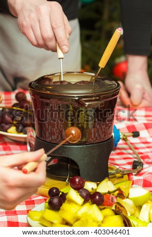 Sweet meal chocolate fondue party with pieces of apples, pears, pineapples and ripe grapes