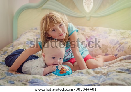 Sweet moment between a big sister and her baby brother. Happy older sister hugging little baby brother lying on parents bed and looking aside. Children watching TV. Adorable family. - stock photo